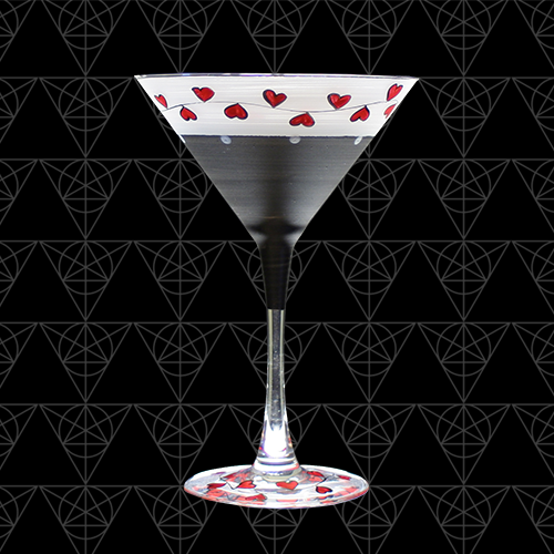 Valentine's Day martini glass we call Valentini. The bowl is grounded in a matte black but lightened up with little red hearts donning the top and base. Hand painted and beautiful.