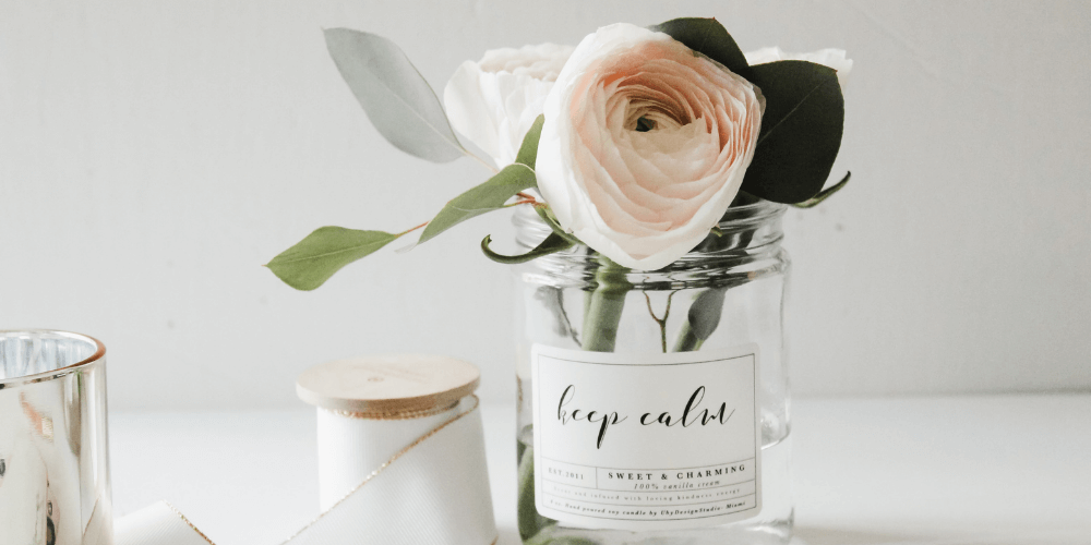 White candle next to a glass jar with pastel pink roses