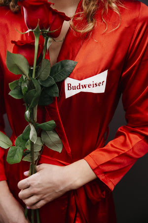 "red satin robe with budweiser logo in white on the upper left chest and ""This Bud's for you"" on the back outline in white"