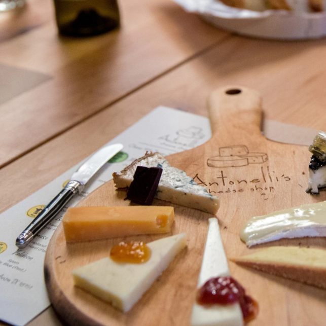 Wooden board with triangular slices of cheese topped with various jams