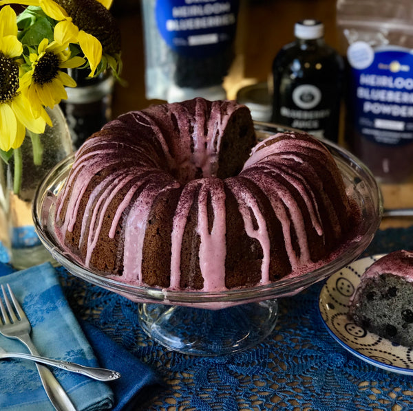 Bundt cake with blueberry icing, blueberry products and sunflowers in background