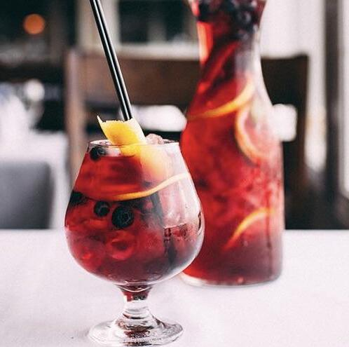 Glass and jug of a festive blueberry sangria