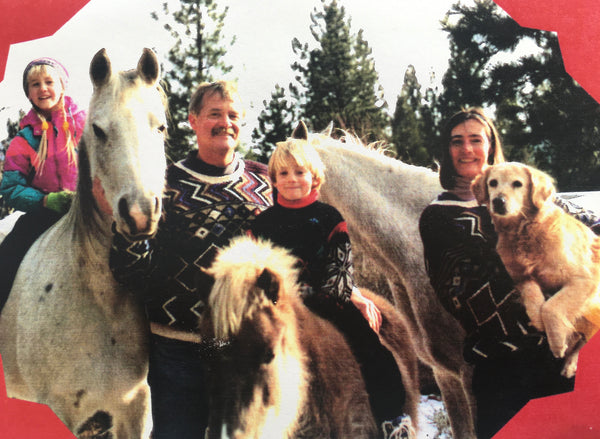 mom, dad, and two kids with three horses and a dog