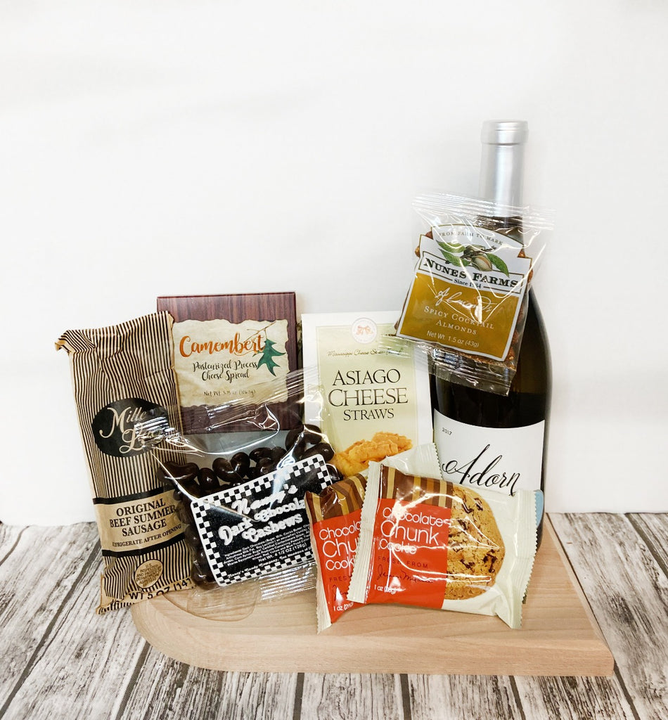 Picnics in the park are a safe way to enjoy each other's company while dining on delicious, gourmet food. This basket features a cutting board for your dining pleasure, a 4.5 oz bag of Dark Chocolate Cashews, 1 5 oz Original Beef Summer Sausage, 1 3.75 oz box of Camembert Cheese, 1 1.5 oz bag of Spicy Cocktail Almonds, 1 3.5 oz box of Asiago Cheese Straws, 1 bottle of Chardonnay and 2 1 oz Chocolate Chip Cookies. You may substitute the Chardonnay for Pinot Noir.