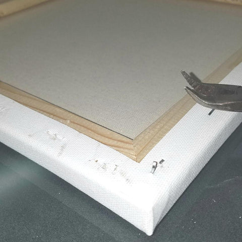 Pulling staples out of a canvas frame for the heat transfer vinyl project