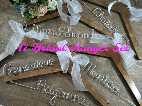 11 wood hangers, walnut stained hangers, wire hanger, names on hangers, wood background, white ribbon, silver wire names