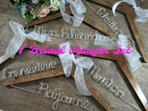 7 Hangers, brown wooden hangers, hangers on brown wood background, personalized hangers, names in silver wire, white ribbon