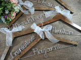 collection of dark wooden hangers, personalized wire hangers, names on hangers, brown background, wedding hangers