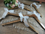 Wire names, white ribbon, Personalized wooden hangers, walnut hangers on wooden background, wire hangers
