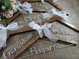walnut hangers on wooden background, wooden hangers, personalized hangers, name hangers, silver wire names, white ribbon