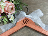 R Monogrammed closeup of cherry stained wooden bridal hanger, white ribbon, pink flower