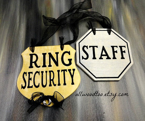 two signs, gray background, ring security sign, staff sign, black ribbon
