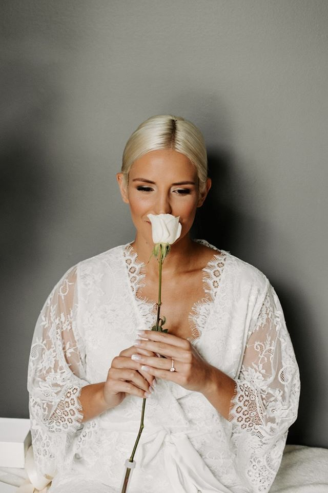 a bride on her wedding day in the Lara Lace lace bridal robe in white from By Catalfo