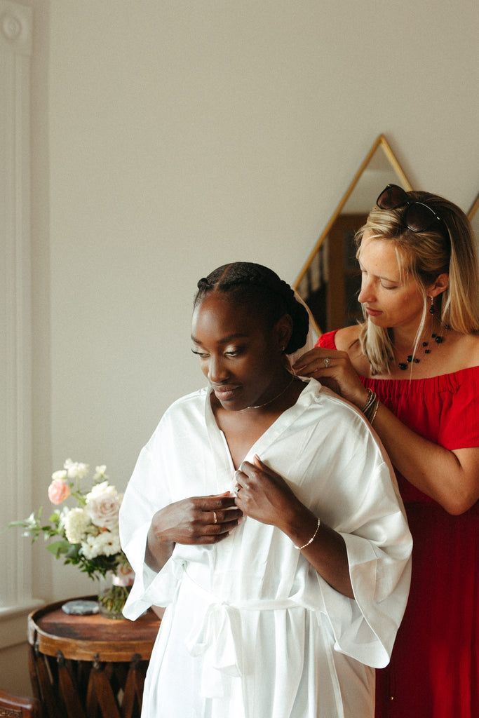 A bride getting-ready in a by catalfo white bridal robe for a Prince Edward County elopement wedding