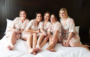bridesmaids on a bed getting-ready wearing by catalfo silk floral robes