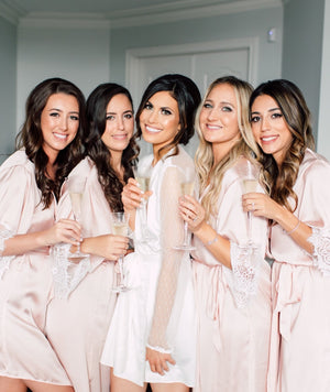 bridesmaids pictured together in blush silk robes with lace sleeves