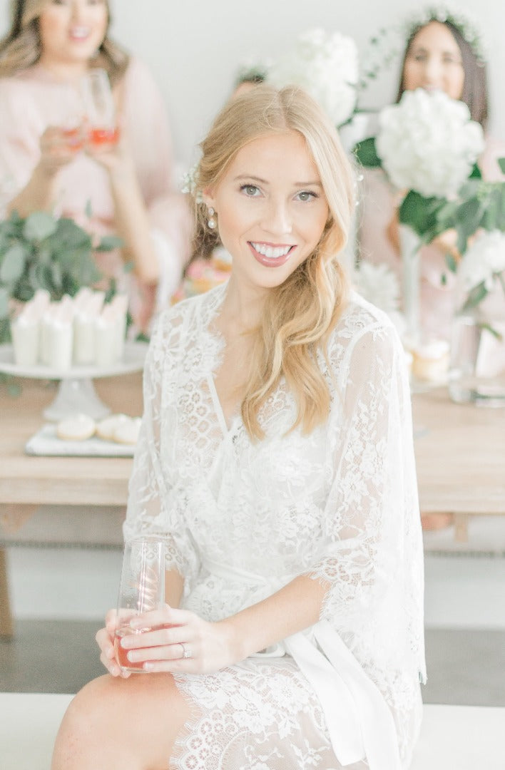 bride wearing a white lace bridal robe for getting ready from By Catalfo