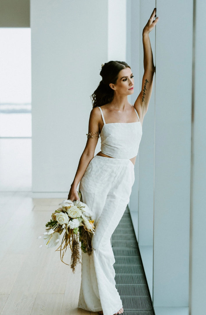 Modern open back, white jumpsuit for wedding rehearsal dinner or bridal shower