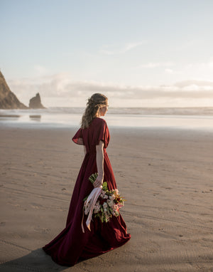 bridesmaid wearing a burgundy wrap dress at haystack rock, oregon