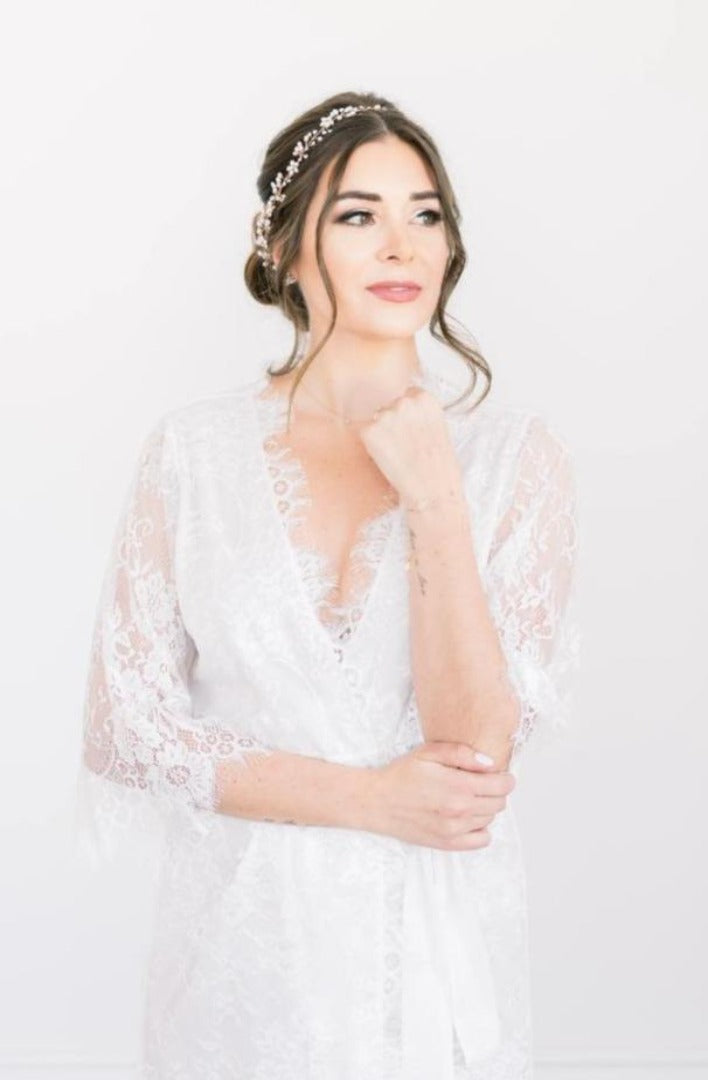 A bride wearing the Lara Robe, a luxurious and modern white lace bridal robe from By Catalfo