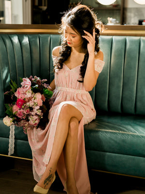 Off the shoulder bridesmaid dress in a blush floral print with bouquet