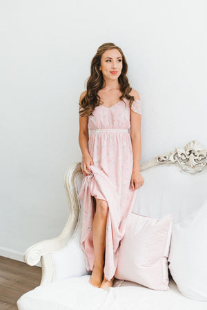 A bridesmaid wearing a modern, blush floral print bridesmaid dress in toronto with off the shoulder sleeves