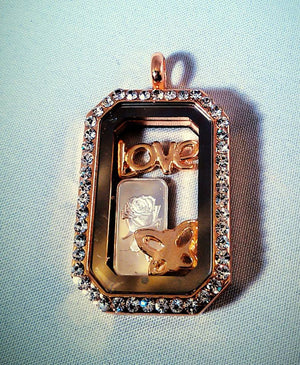 A story locket with rinestones, a stamped silver gram with a rose, love, and butterfly