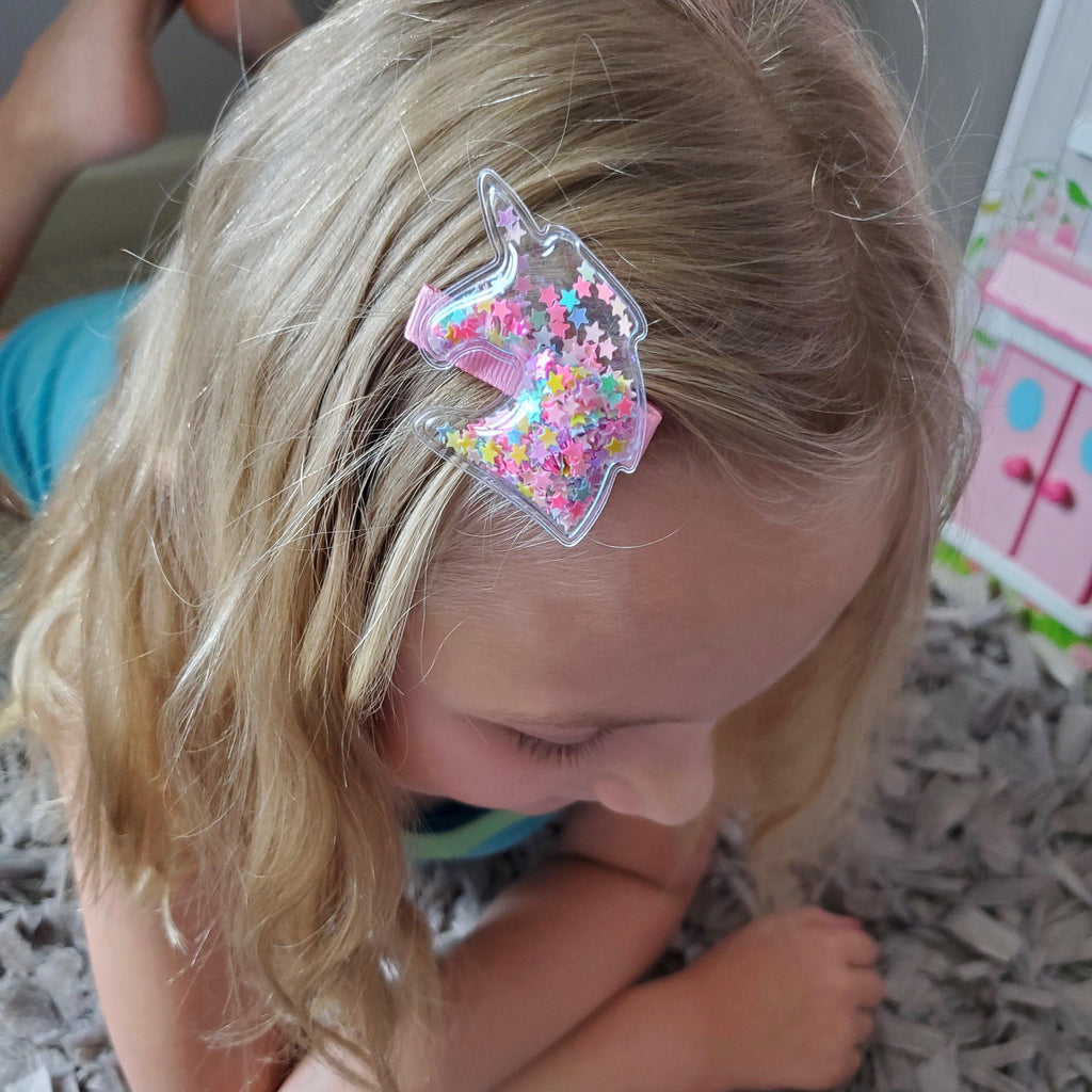 little girl wearing a unicorn glitter shaker no slip hair clip