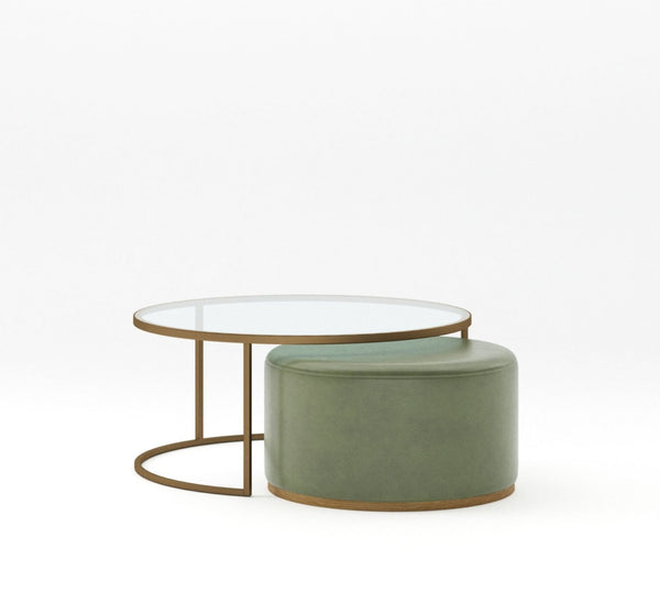 Large coffee table with round glass top and medium bronze metal powder coated frame with khaki green leather smaller ottoman nested below with medium bronze metal base on plain white background