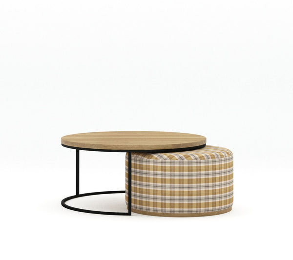 Blonde Oak round top large coffee table with matt black metal powder coated base frame with smaller plaid fabric upholstered ottoman with blonde oak base nestled underneath on plain white background