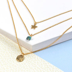 Close up of Birthstone Layered Charm Necklace gold