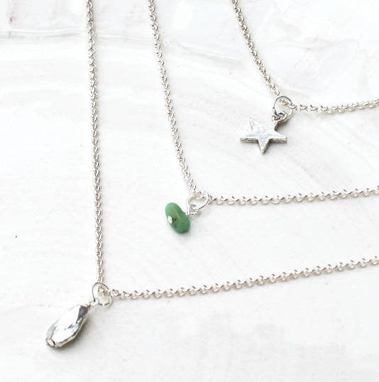 Close up of sterling silver Birthstone Layered Charm Necklace