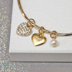Close up of gold bangle with diamante heart and additional pearl
