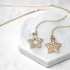 Close up of Diamante Star Thread Through Earrings gold