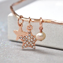 Close up of rose gold personalised bangle with diamante star and added freshwater pearl