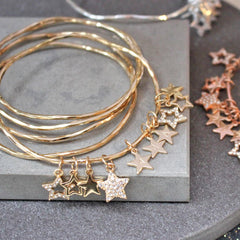 Close up of personalised diamante star bangles in gold