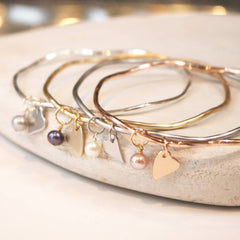 Personalised bridesmaid presents bangles with heart charms.