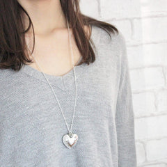 Silver hammered heart pendant with personalised heart charm worn by model