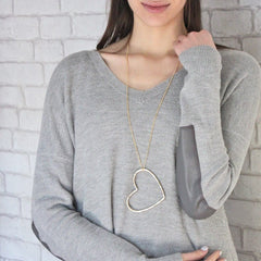 Gorgeous large heart necklace hanging from long chain in gold worn by model