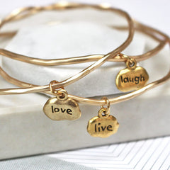 Close up of gold Live Love Laugh Mantra Bangles set