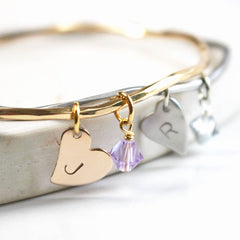 Close up of gold and silver personalised bangles with heart charms and Swarovski crystal