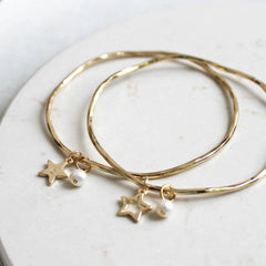 24ct gold plated bangle with open or solid star charm and a freshwater pearl