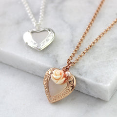 Close up of rose gold vintage heart locket with peachy pink rose