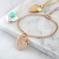 Rose gold vintage heart locket with gold and silver in the background