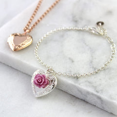 Silver vintage heart locket bracelet with mauve rose and rose gold vintage heart necklace in background