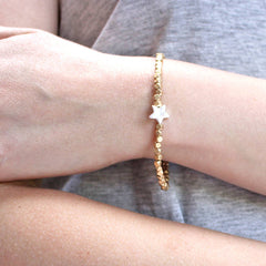 Close up of Gold Bead Charm Bracelet with star charm