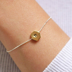 Hand stamped R hexagon bracelet in gold worn by model