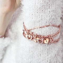 Close up of rose gold diamante heart charm personalised bangle set worn by model