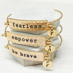 Stacking gold mantra bracelets; fearless, empower and be brave