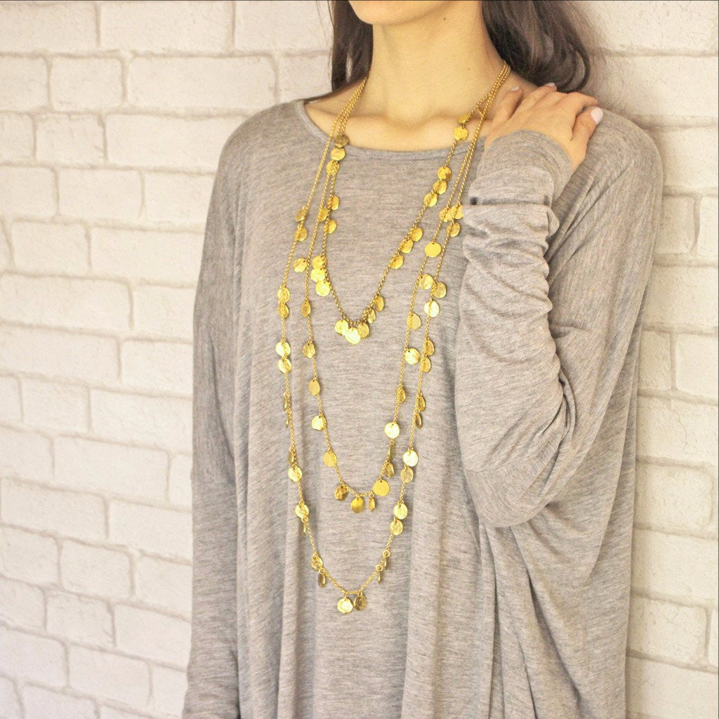 Set of three chains of gold necklaces on model